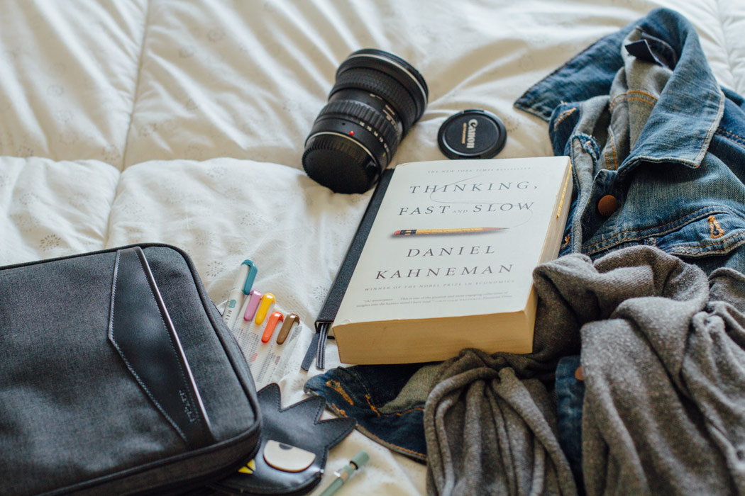 Organizer, in-flight reading, camera lens, denim jacket, scarf, lens cap, and a few pens.