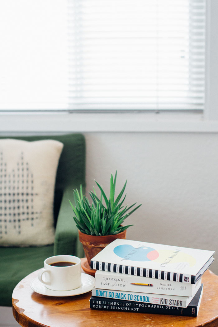 A stack of summer reading, a small potted aloe vera, and a cup of coffee on a wooden coffee table